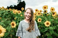 happy tween girl standing in a field of sunflowers