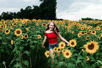 teenage girl in a red top running through a field at anderson sunflowers