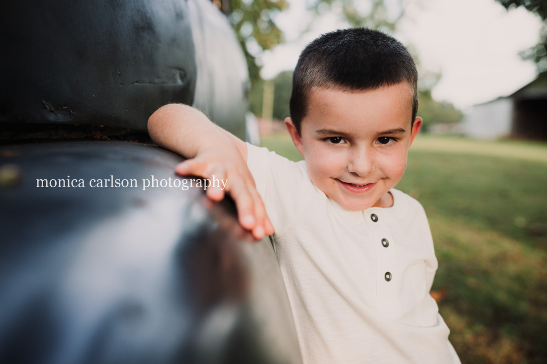 portrait of a boy leaning against a pick up truck