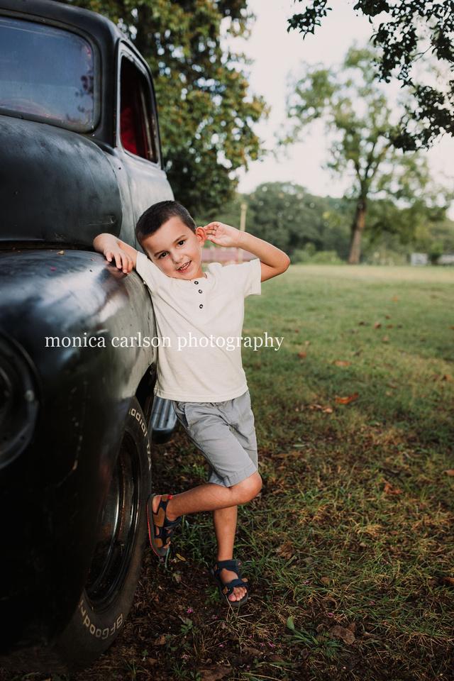 boy leaning against a antique truck in cumming, ga