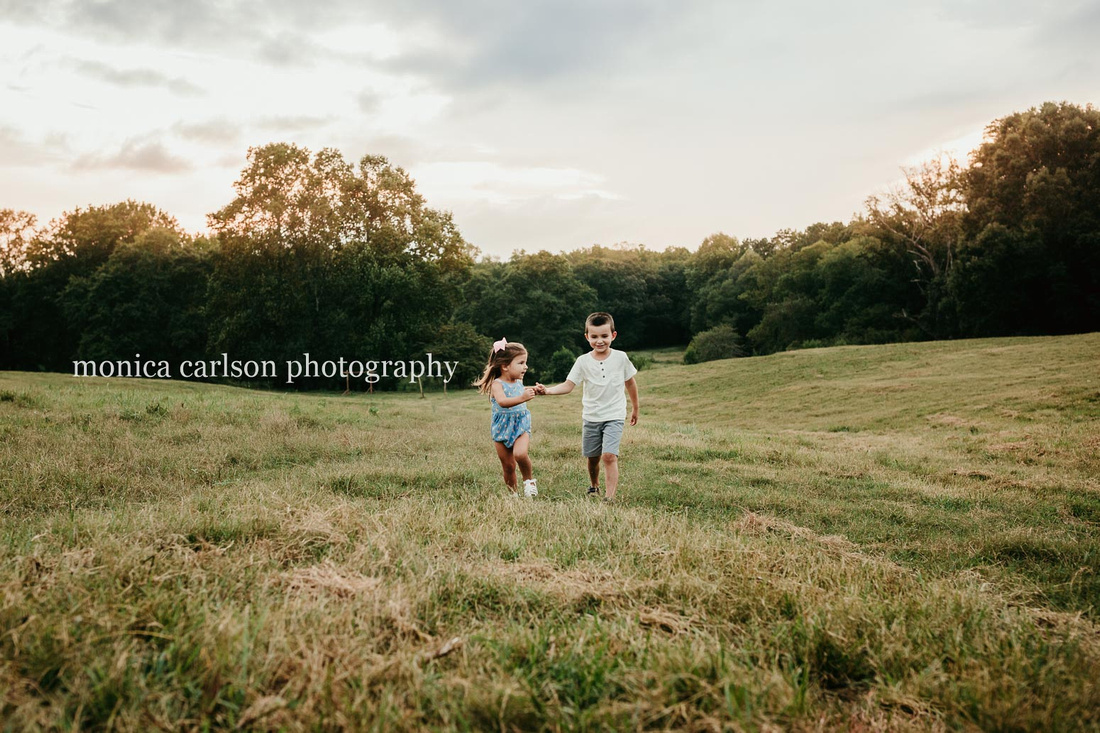 siblings running on a open field by monica carlson photography