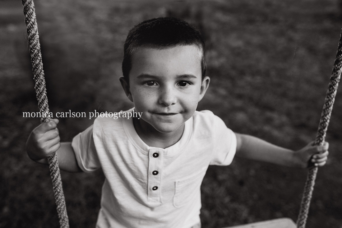 black and white portrait of a boy on a tree swing