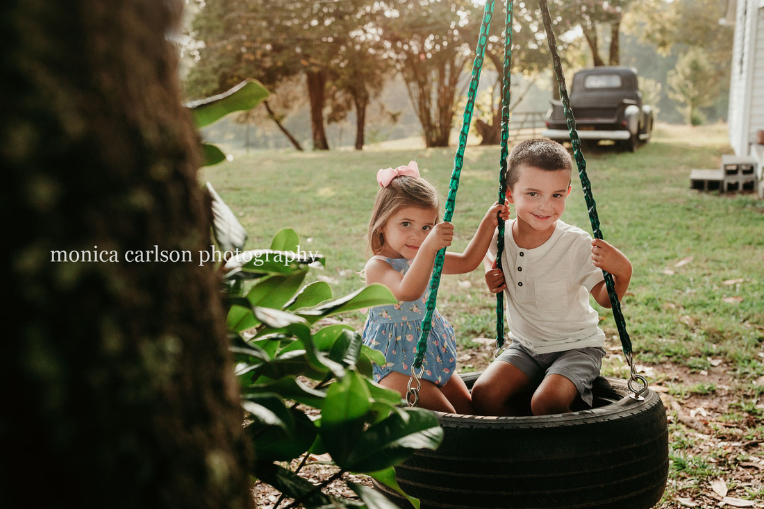 brother and sister sitting on a tire swing at milford family farm in cumming