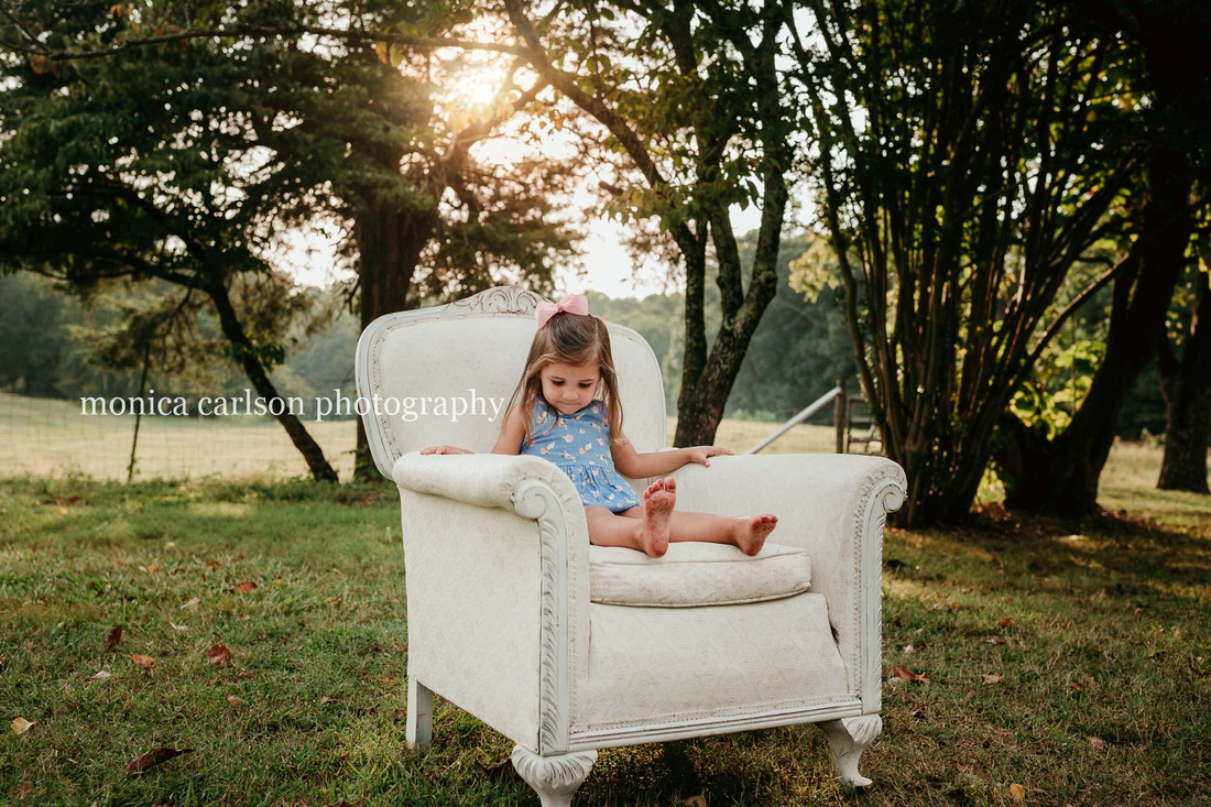 little girl sitting on a big chair under a tree at sunset