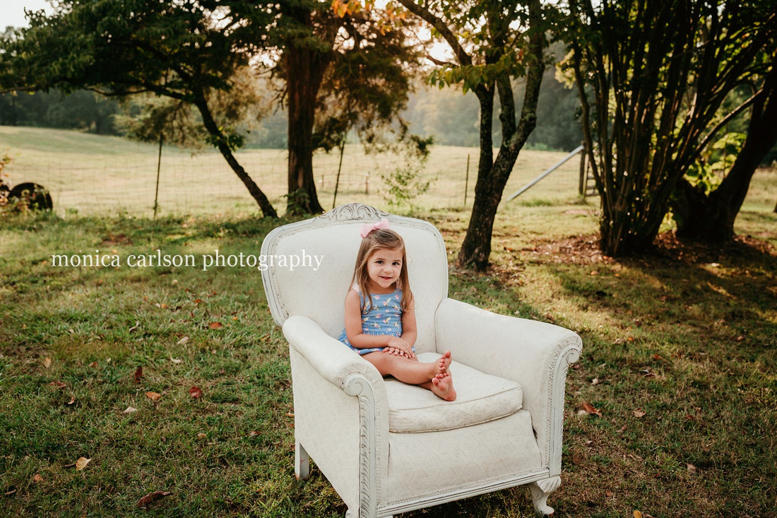 sweet smiling little girl sitting on a big white chair on a farm in cumming, ga