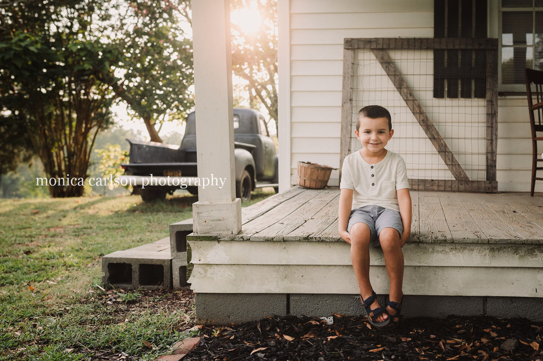 sweet little boy sitting on a wooden porch at a farm in cumming