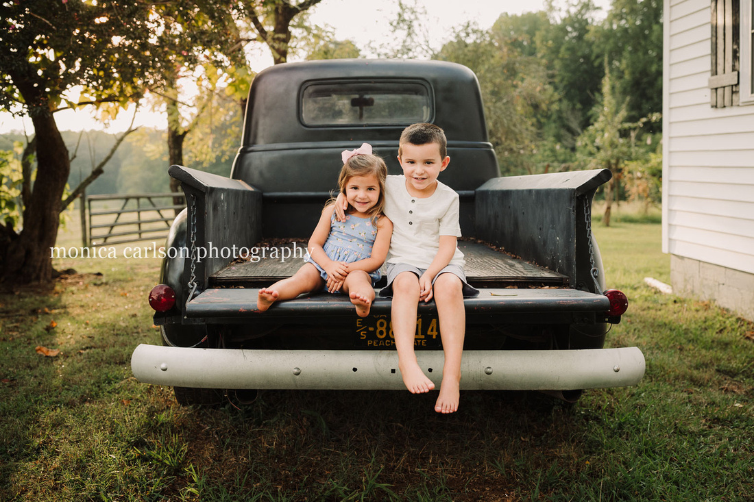 adorable siblings sitting on a old truck during a photo session with monica carlson photography