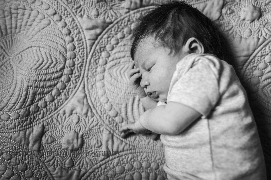 baby boy sleeping on his side during a in home newborn session