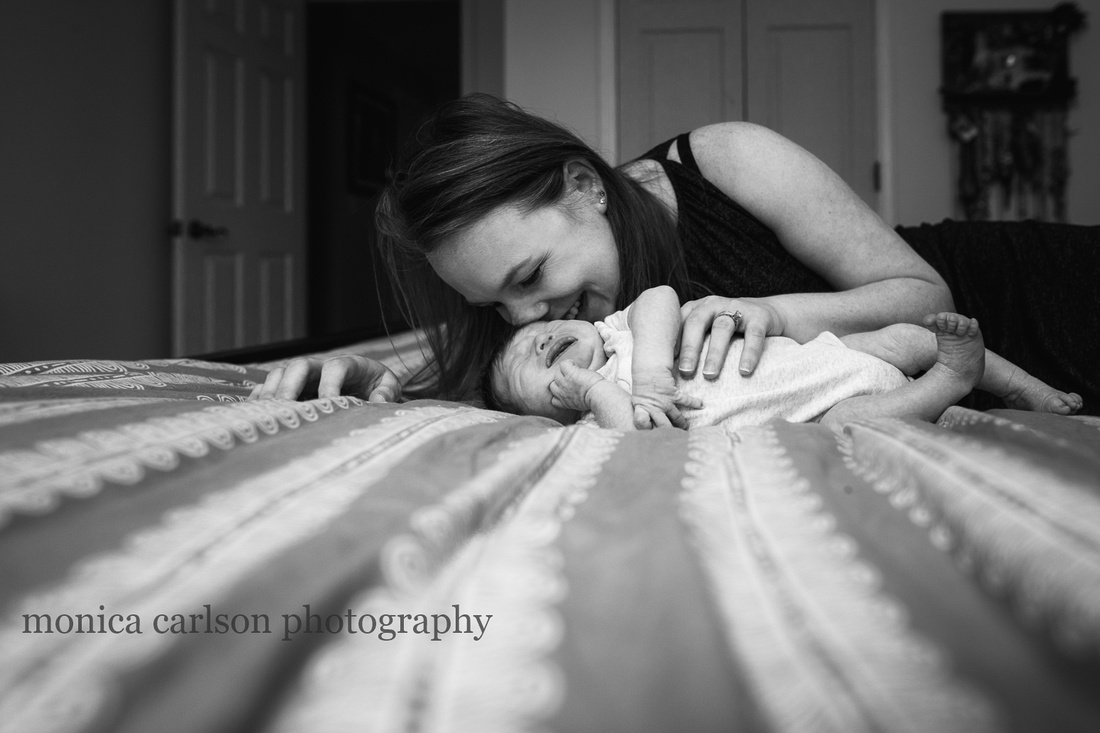 mother snuggles a crying baby on her bed