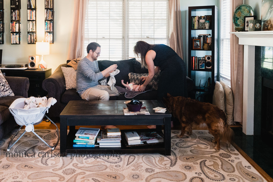 lifestyle photo of parents dressing their new baby at home in atlanta