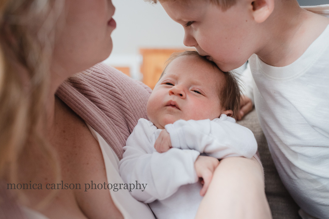 Big brother kissing his new baby sister in Alpharetta