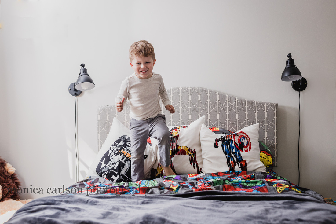 Boy jumping on his bed at a home photo session in alpharetta