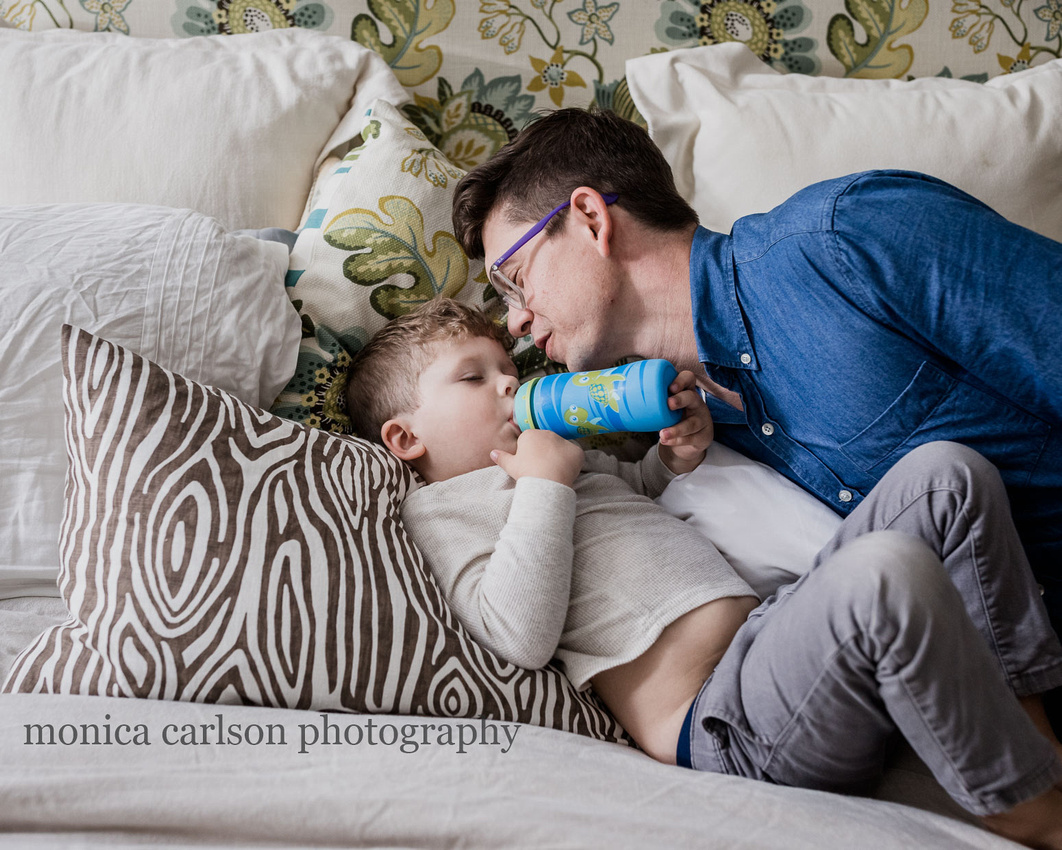 boy having a drink in bed while his dad watched him in Alpharetta
