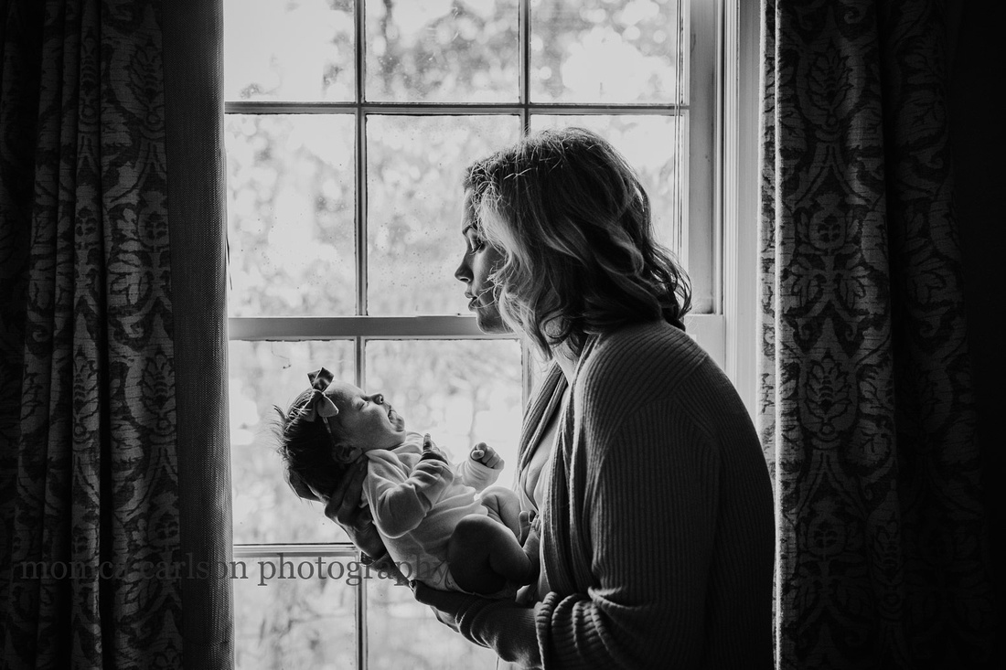 Mother holding her baby by a nursery window in alpharetta
