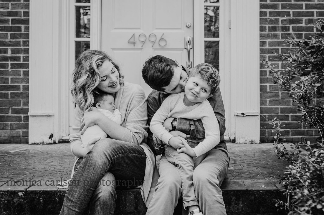 little boy making a funny face with his family outside their home