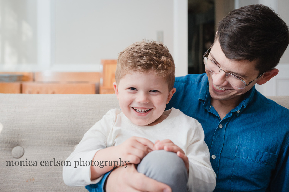 Dad and his son laughing on the couch at home