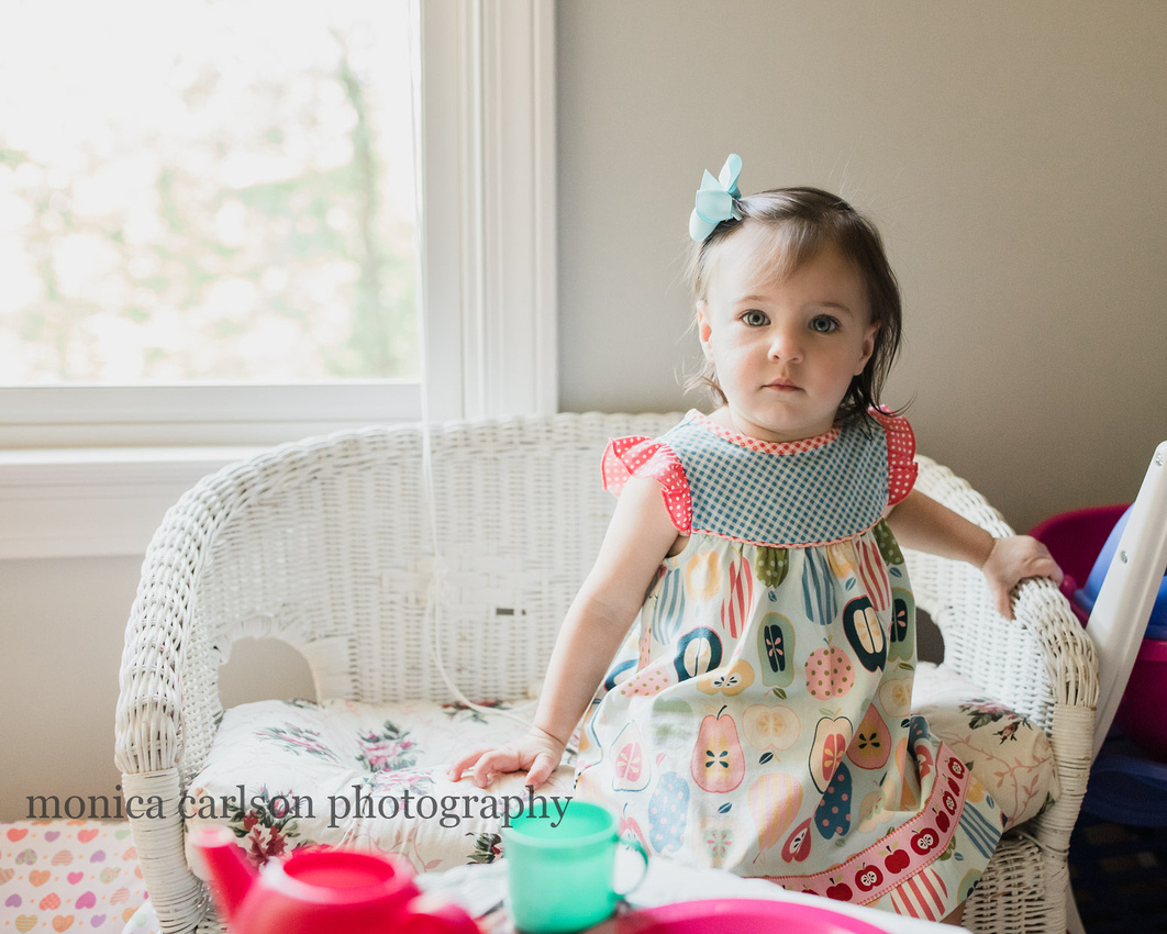 Little girl sitting in her playroom during a in home photo session