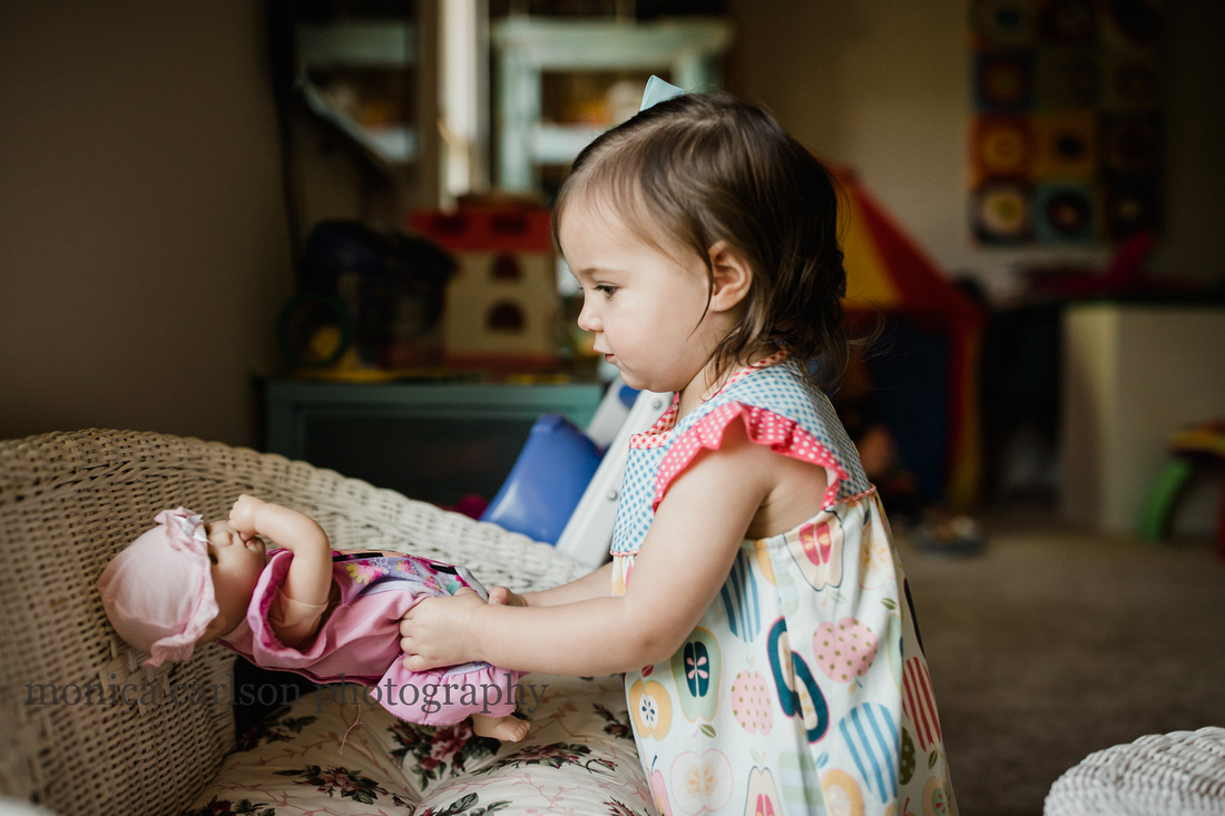 two year old girl playing with her baby dolls at home in Alpharetta