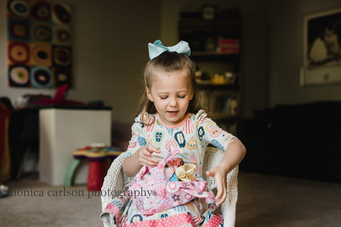 little girl playing with her dolls during a home lifestyle photo session