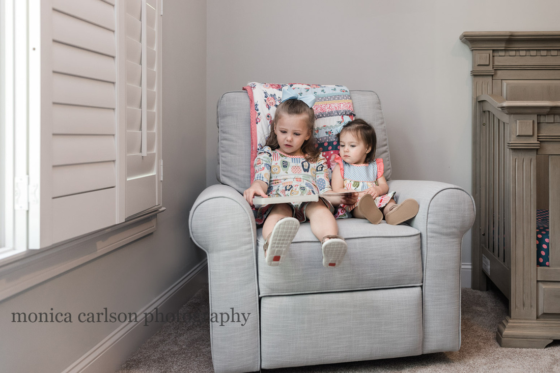 sisters sitting together in a chair reading a book in their room during a lifestyle photo session
