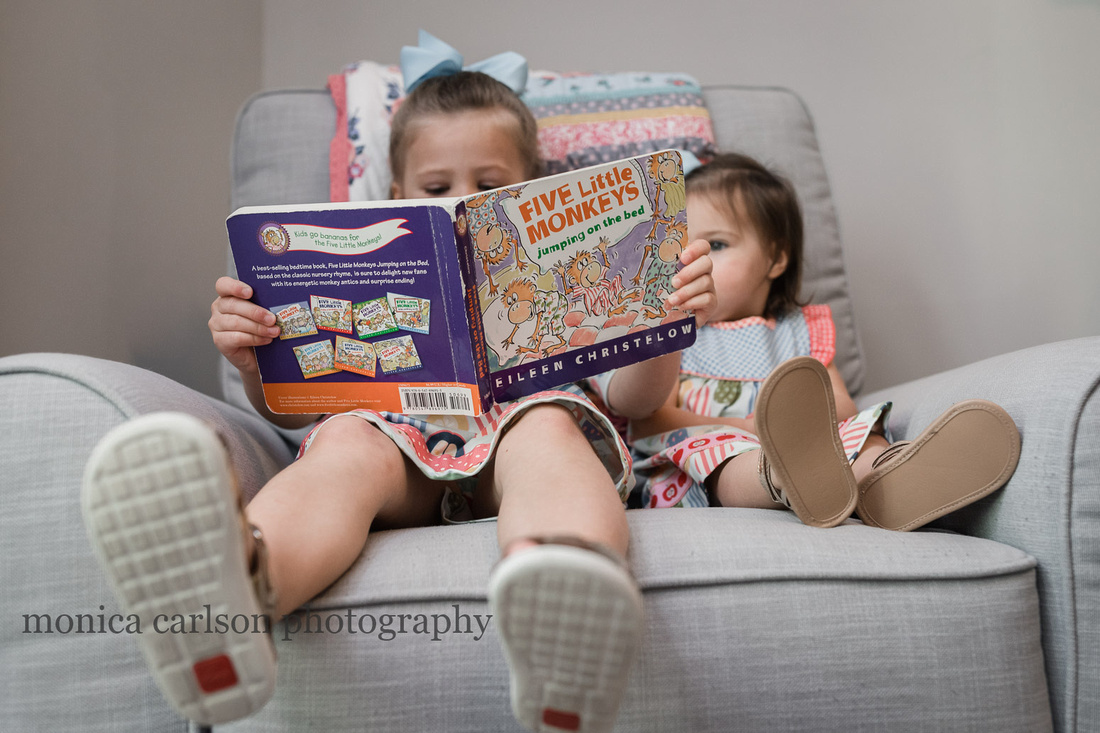 Two girls reading a book at home in Alpharetta