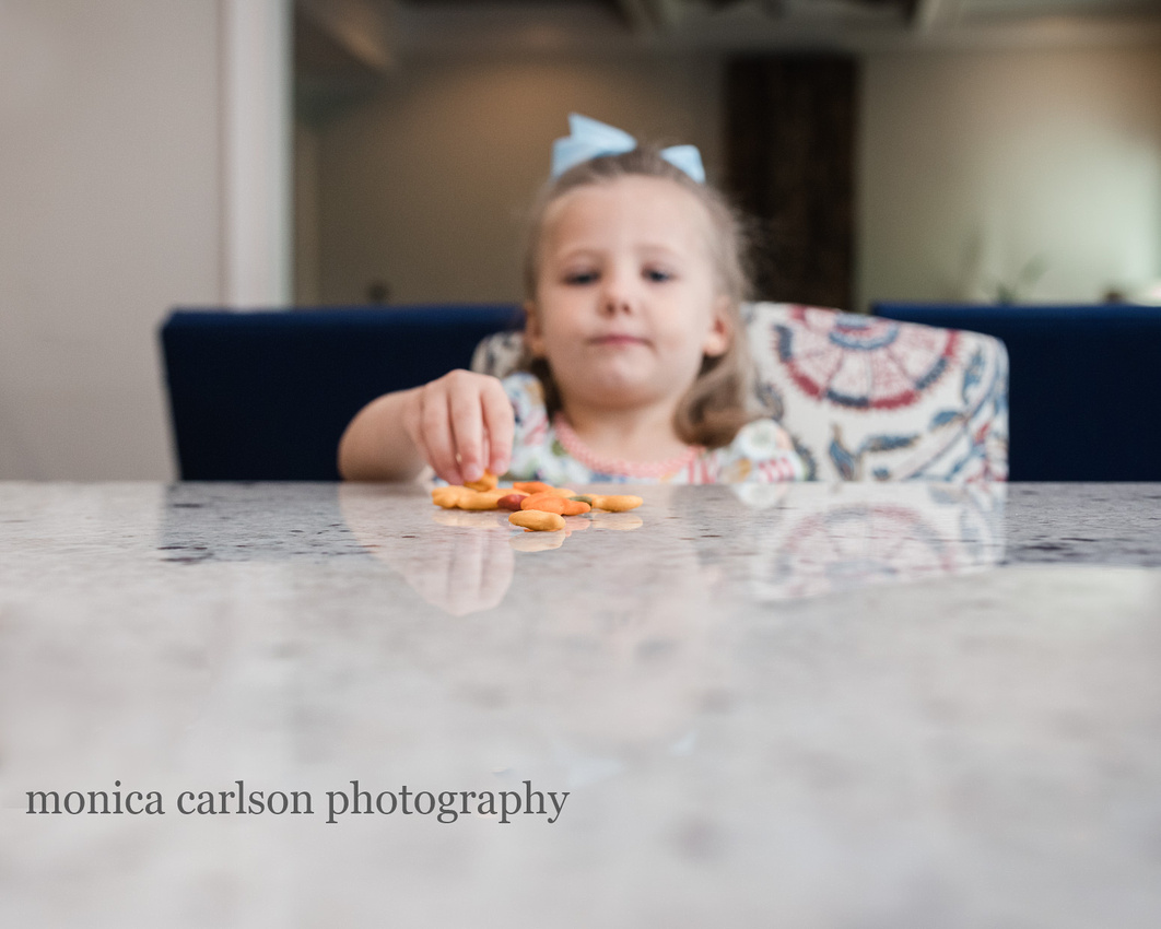 girl eating goldfish in her home kitchen