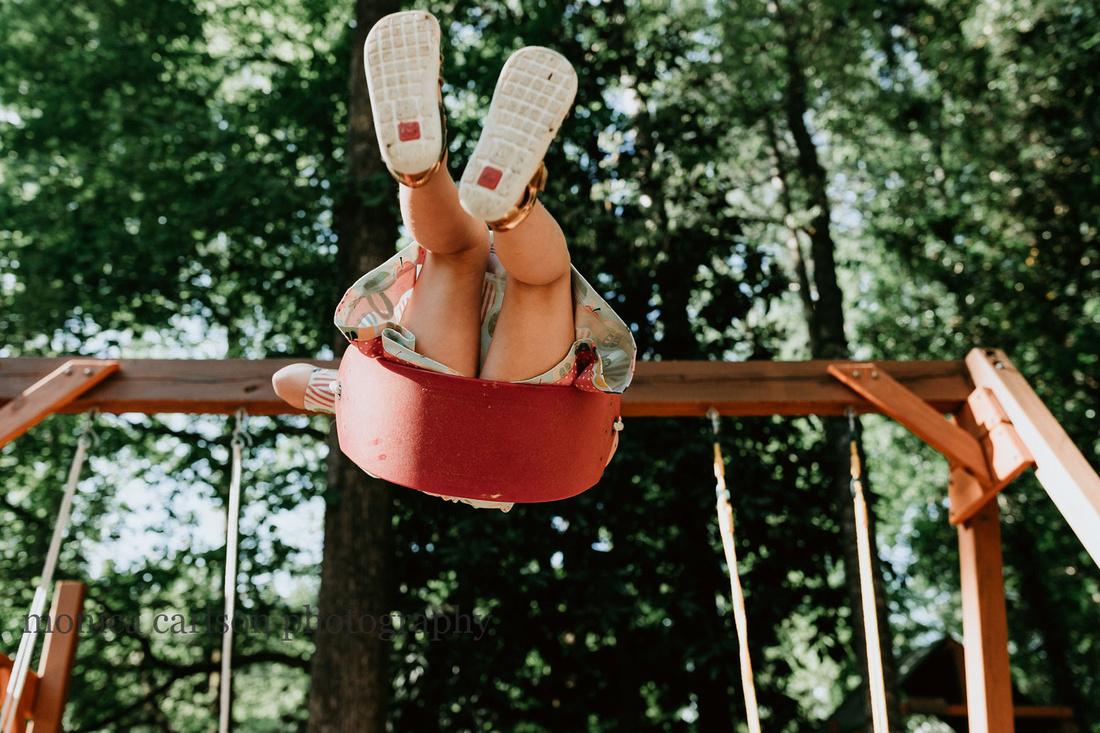 little girl on a swing in her yard outside atlanta