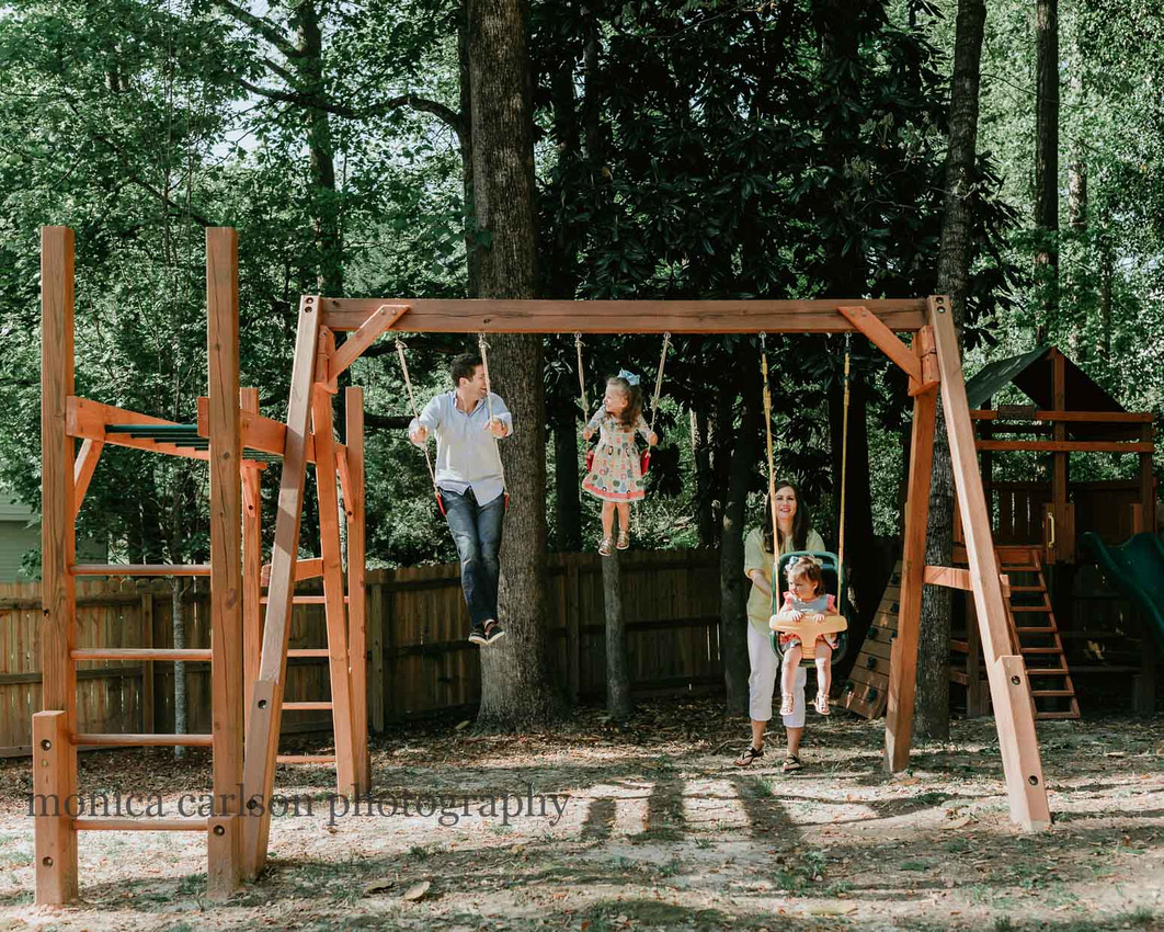 Family of four playing on their backyard playground during a home lifestyle session