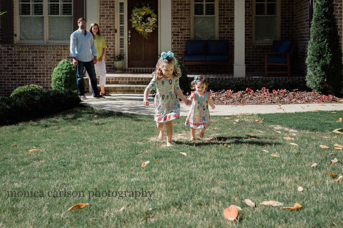 two sisters running in front of their home in Alpharetta while their parents watch