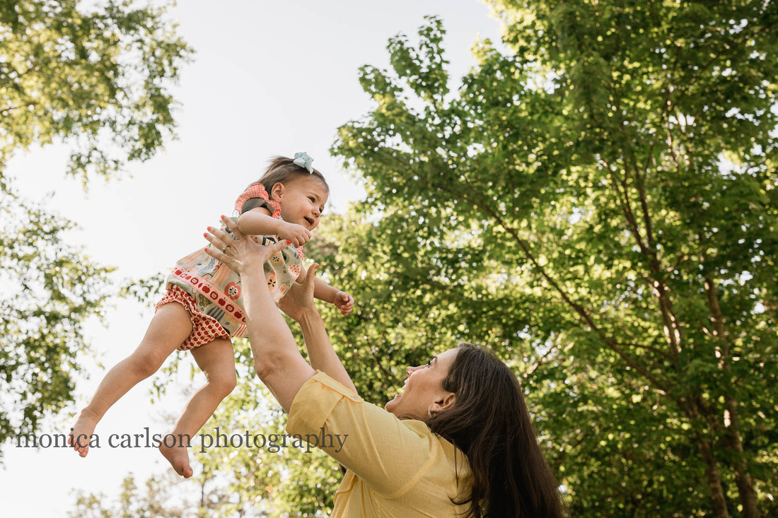 girl being tossed in the air by her mother during a family photo session