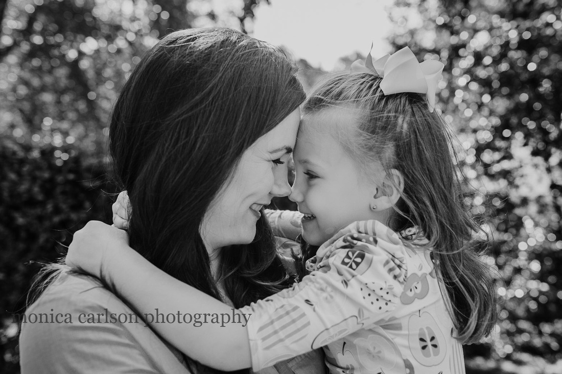 portrait of a mother and daughter giving eskimo kisses during a home photo session