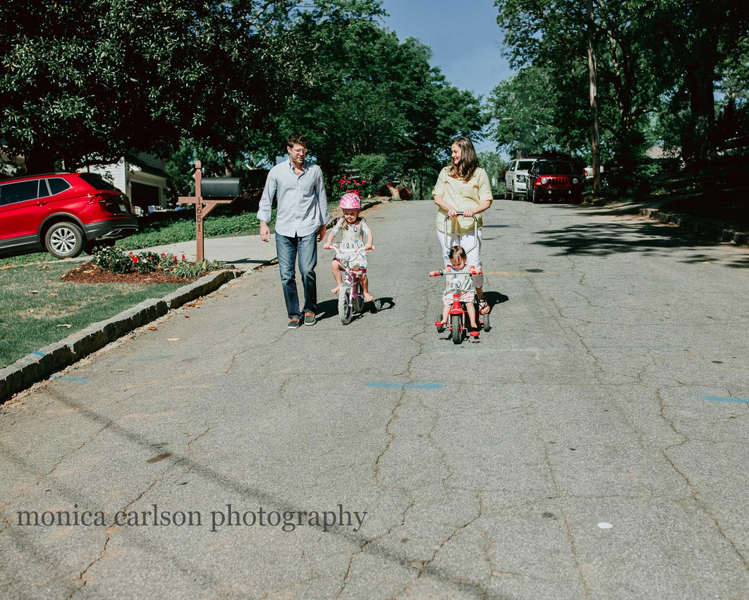 family outside their home taking a bike ride during a home photography session