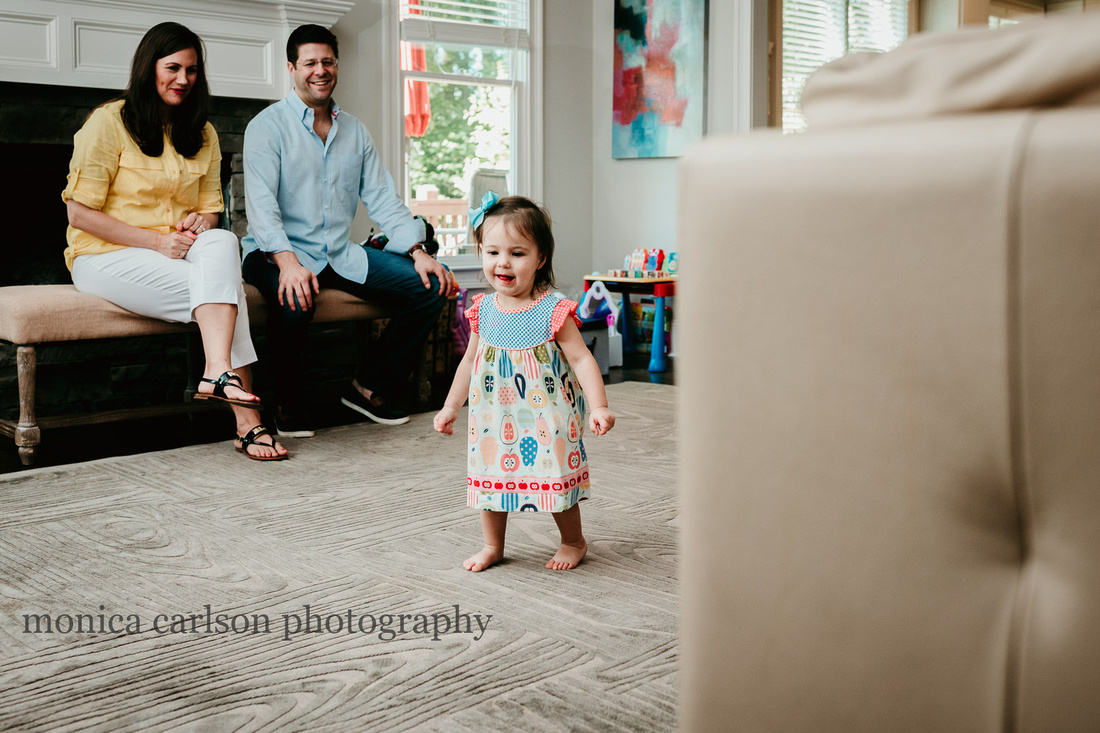 little girl dancing in her living room while her parent watch and laugh during a family photo session