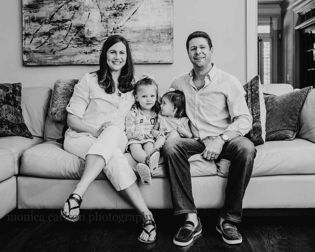Black and white portrait of a family on their living room couch