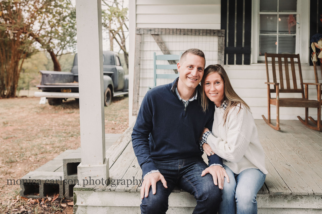 husband and wife sitting on a white wooden porch