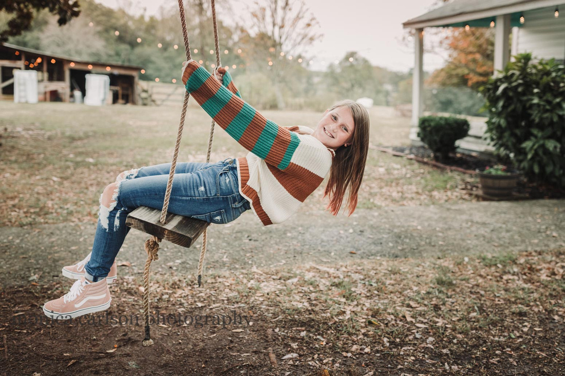 teen girl on a wooden tree swing on a farm in cumming during a family photo session