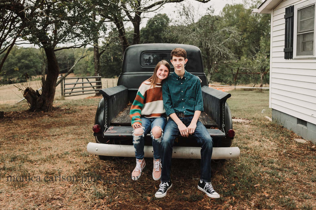 teenage brother and sister sit on the bed of a antique truck on a farm in Cumming, GA