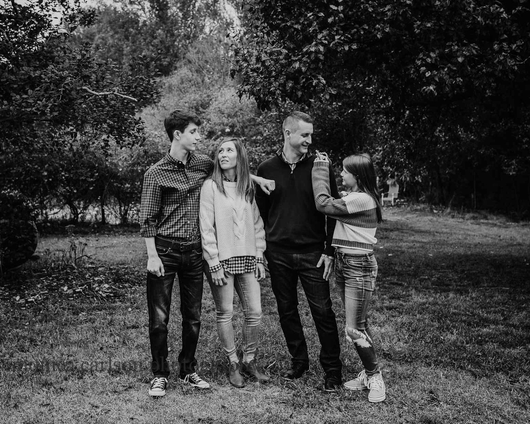 black and white image of a family of four laughing together on a farm by monica carlson