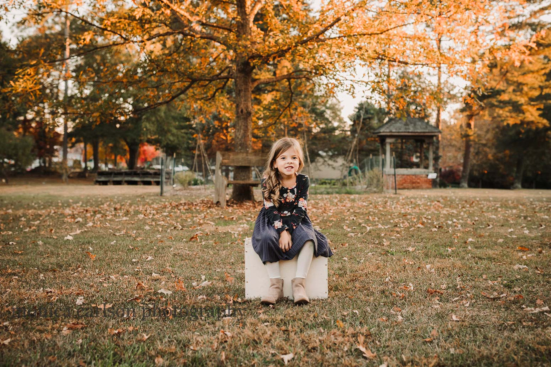 cute little girl sitting on a box with beautiful fall foliage behind her in Roswell, Georgia