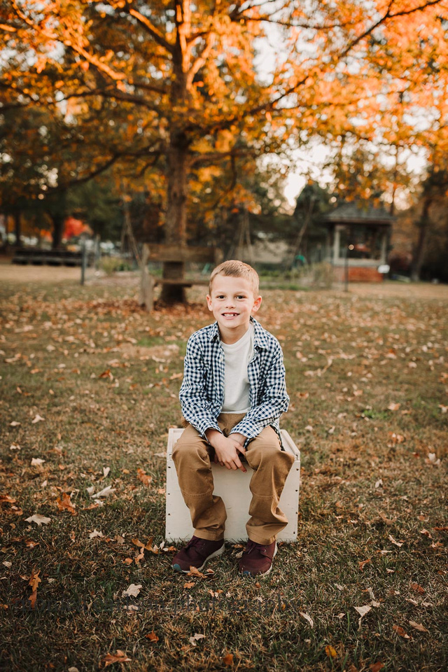 little boy sitting on a box with fall leaves behind him in Roswell, Georgia