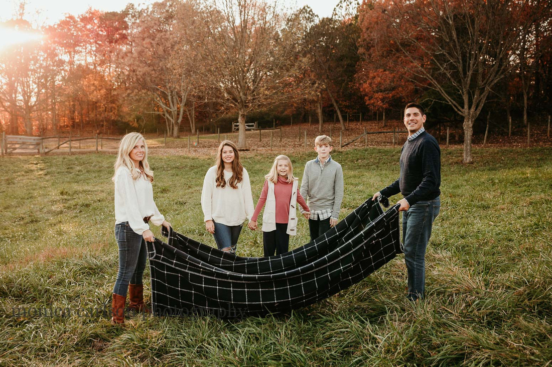 family of five get ready to play a game with a blanket