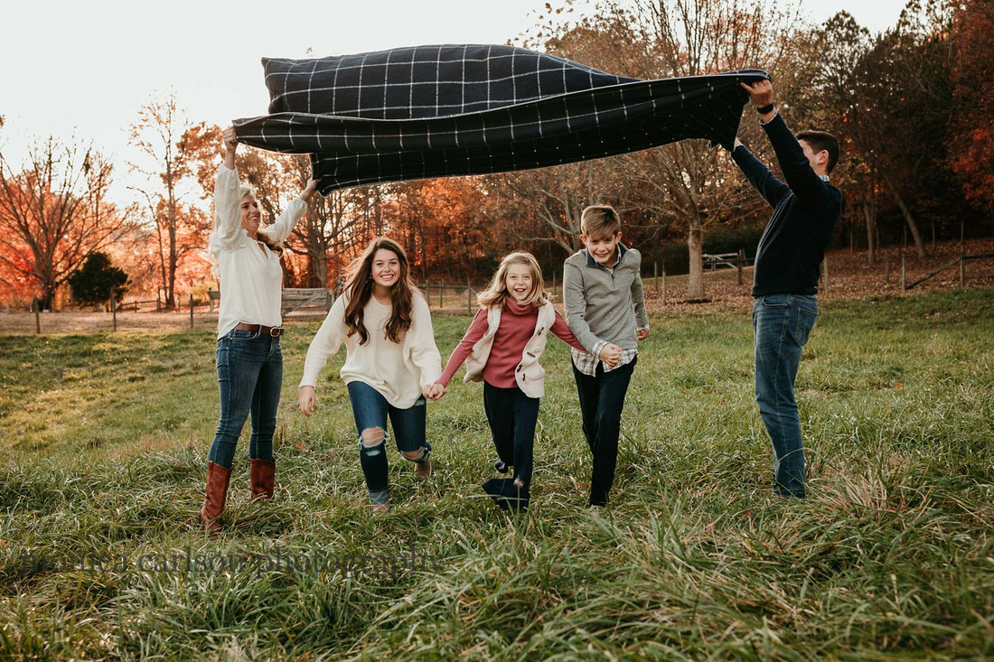 siblings run beneath a blanket their parents are creating a tunnel with