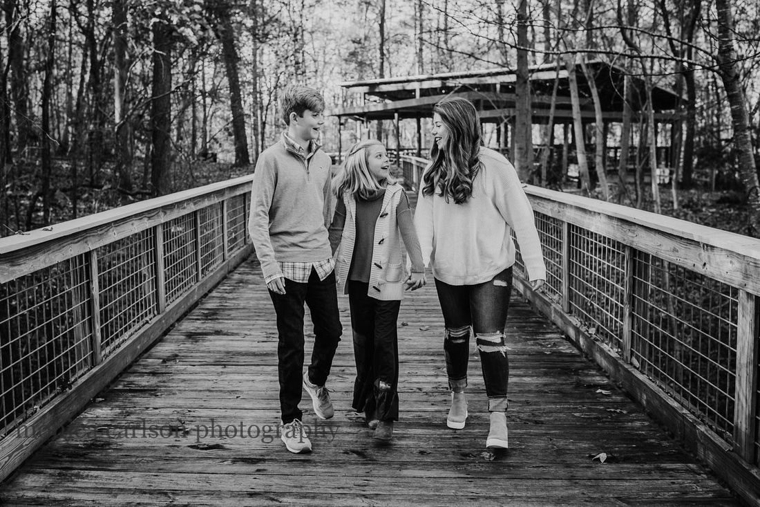 black and white portrait of three siblings walking on a bridge during a family photo session