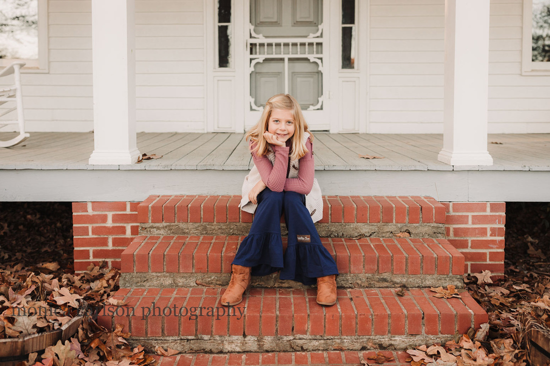 tween girl sitting on the steps of a white wooden house