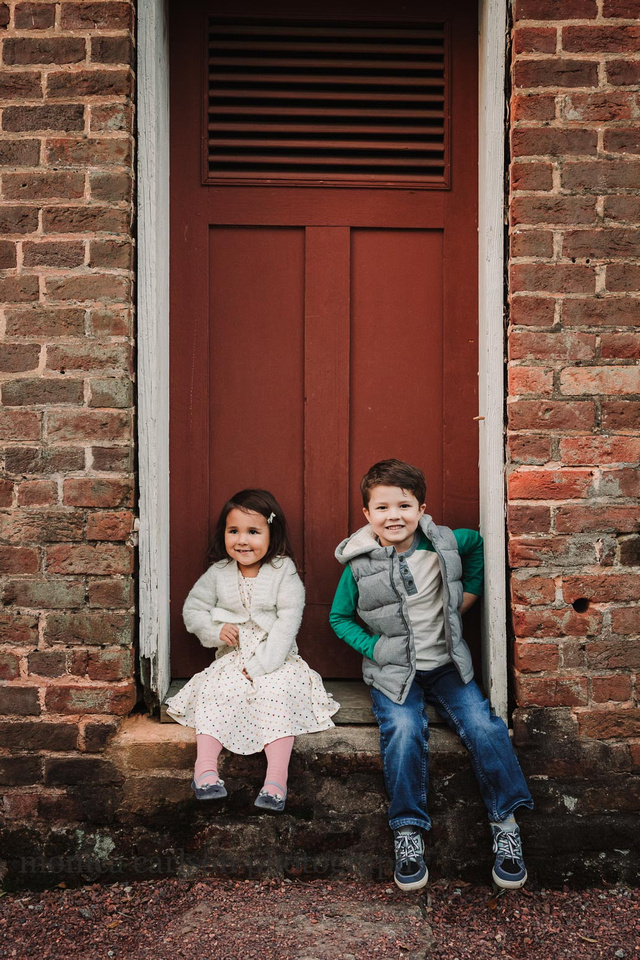 brother and sister sitting in front of a red door at Barrington Hall