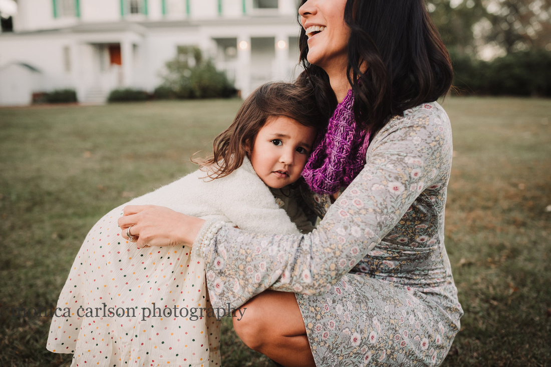 little girl holding on to her mother while mom laughs taken by monica carlson