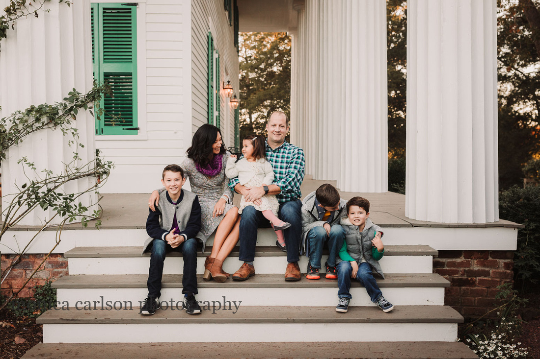family of six sitting on the steps of Barrington Hall