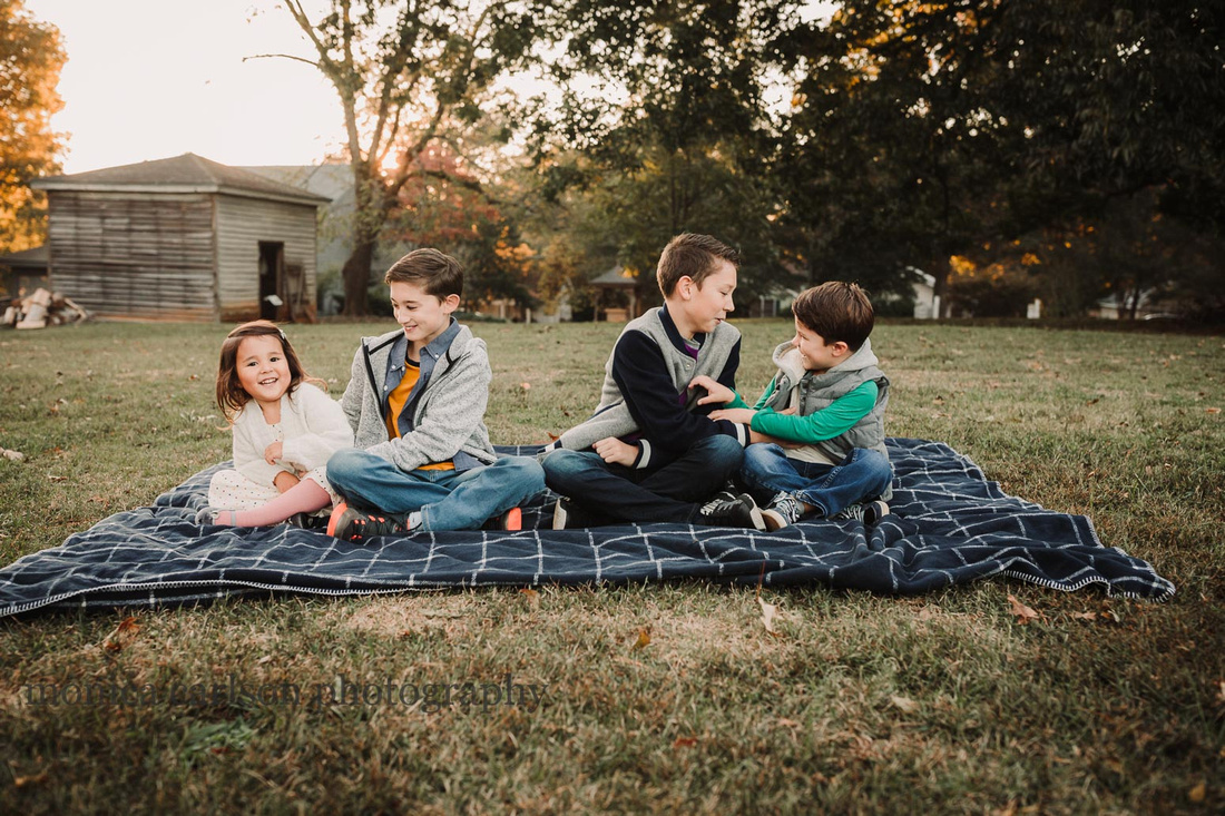 four kids sitting on a blanket tickling each other