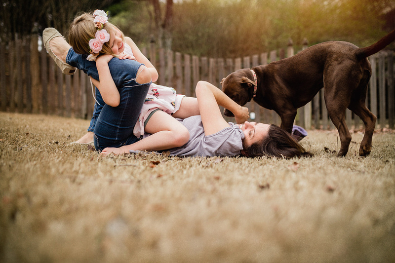 woman laying on the ground while a child grabs her leg and dog kisses her face