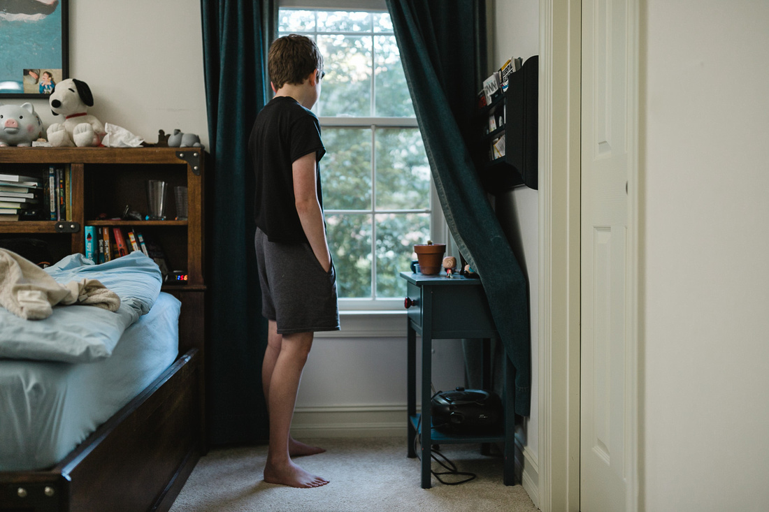 boy looking out the window of his room after just getting up